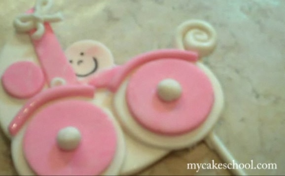 This sweet baby carriage cake topper would be perfect for baby shower cakes! Video tutorial by MyCakeSchool.com