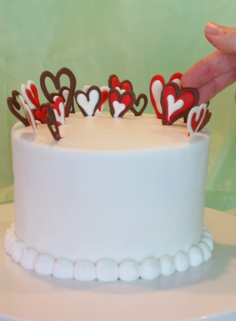 Adorable and simple Valentine's Day Cake by MyCakeSchool.com featuring chocolate hearts! Free cake decorating tutorial!