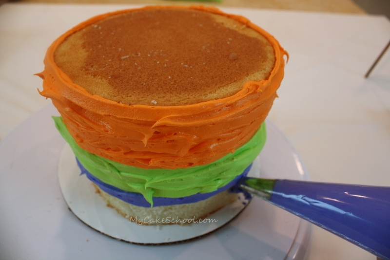 Learn to make a Witches Cauldron and tri-colored buttercream in this free Halloween Cake Tutorial by MyCakeSchool.com!