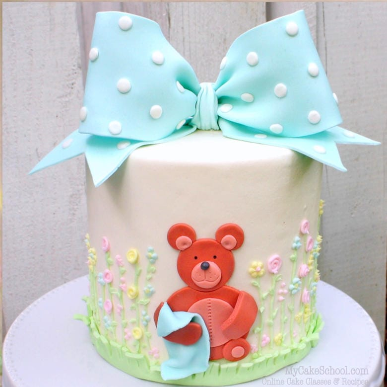 CUTE teddy bear cake with classic bow and sweet piped buttercream flowers! Member cake video tutorial section- MyCakeSchool.com
