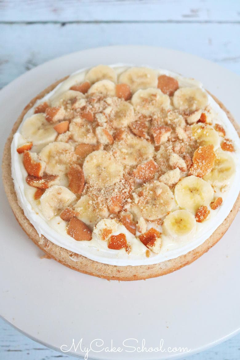 This Banana Pudding Cake recipe from scratch is an amazing combination of banana cake, crushed Nilla wafers, sliced bananas, and frosted with cream cheese frosting.