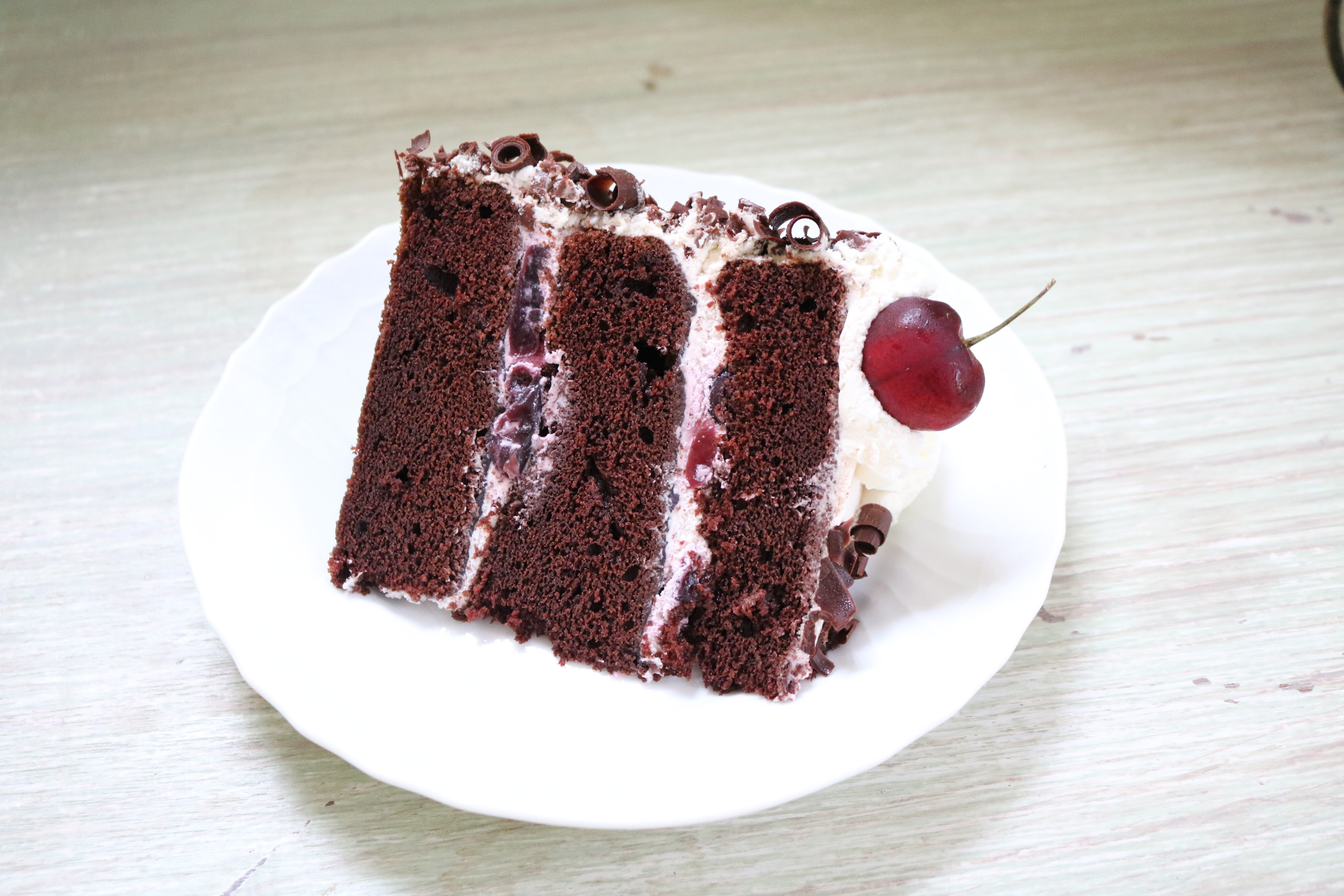 This Black Forest Cake From Scratch is the Best! Chocolate cake infused with Cherry Liqueur and filled with whipped cream and cherries!